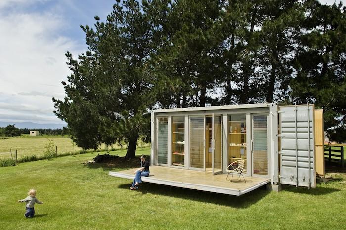 hier ist eine unserer ideen für ein schönes container haus mit terrasse und mit einem garten mit grass und bäumen und kindern
