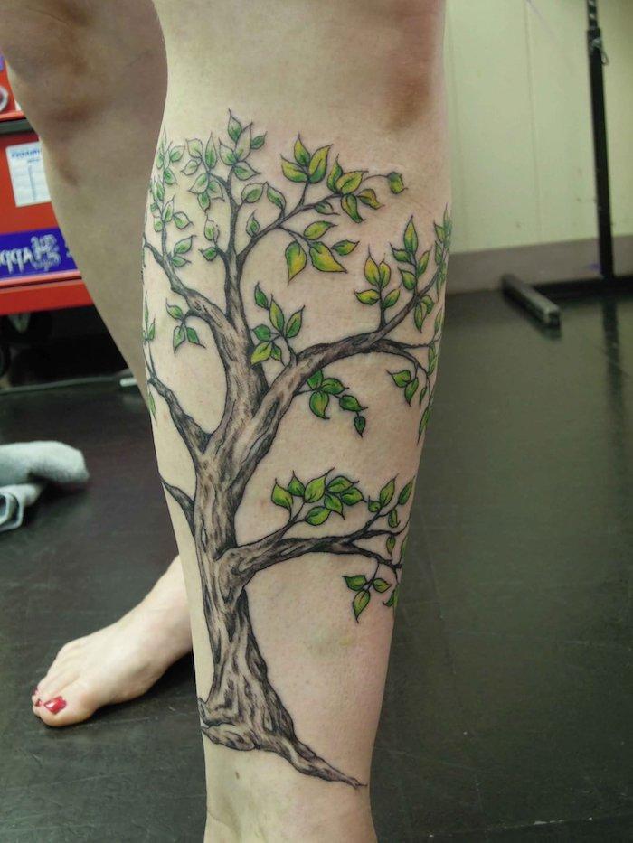 Lebensbaum Tattoo mit kleinen grünen Blätter, viele Zweige Tattoo am Bein