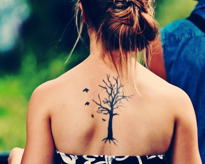 ein dünnes Tattoo Lebensbaum mit ein paar kleinen Vögelchen, die losfliegen