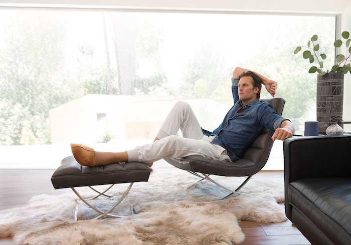 hochwertige beige hausschuhe aus leder, mann mit blauer hose und dunkelblauem hemd