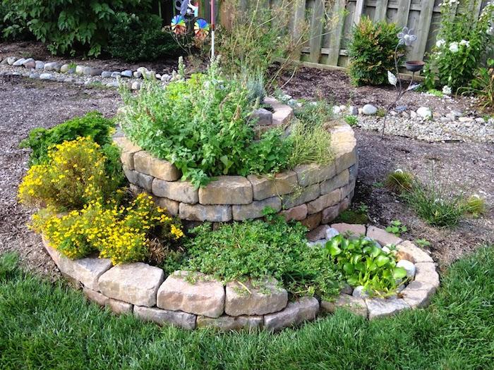 hier zeigen wir ihnen eine unserer ideen zum thema kräuterspirale selber bauen - eine kräuterschnecke mit grünen pflanzen nd weißen steinen