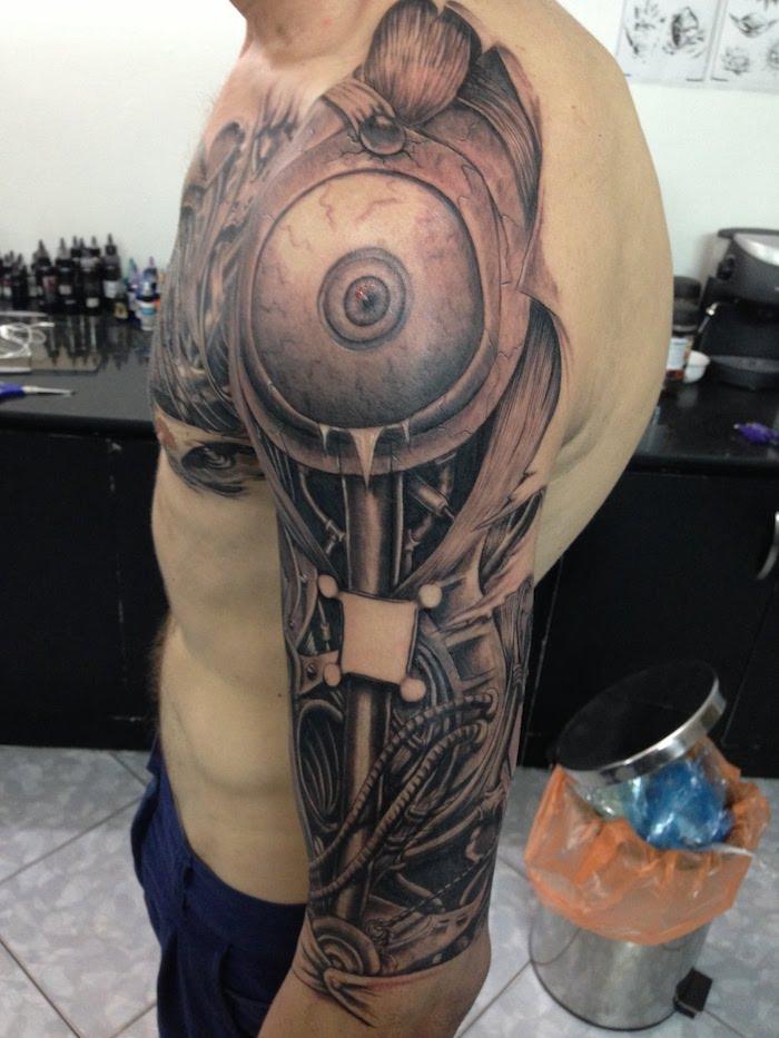 mann mit schwarz-grauem oberarm tattoo mit maschinenteilen