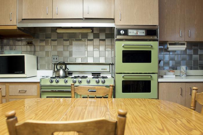 eine gemütliche Wohnküche mit einem alten Ofen in grüner Farbe und Möbel aus Holz