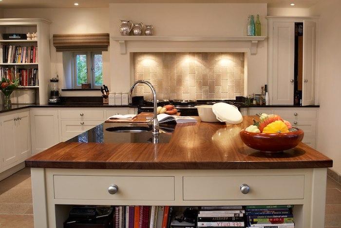 Wohnküche mit Kochinsel, indirektes Licht und Arbeitsplatte aus Naturholz, ein Bücherregal