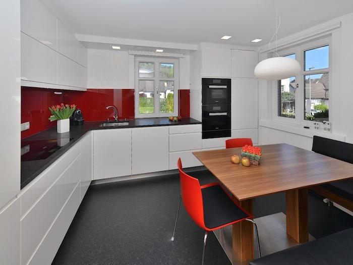 Wohnküche mit bequemem Tisch aus Hock und ein Ecksofa und roter Stuhl