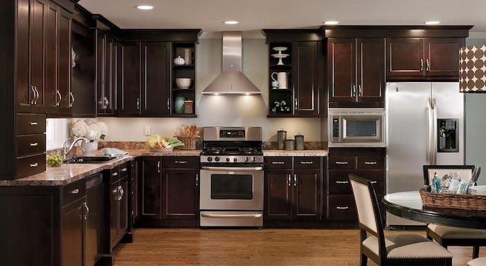 Ikea Wohnküche in dunkler Farbe mit modernen elektrischen Geräte und Tisch aus Massivholz