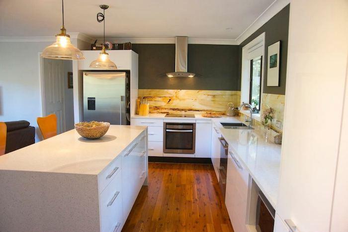 Wohnküche mit weißer Ausstattung, grau gestrichene Wände, Laminatboden und bunte Fliesen