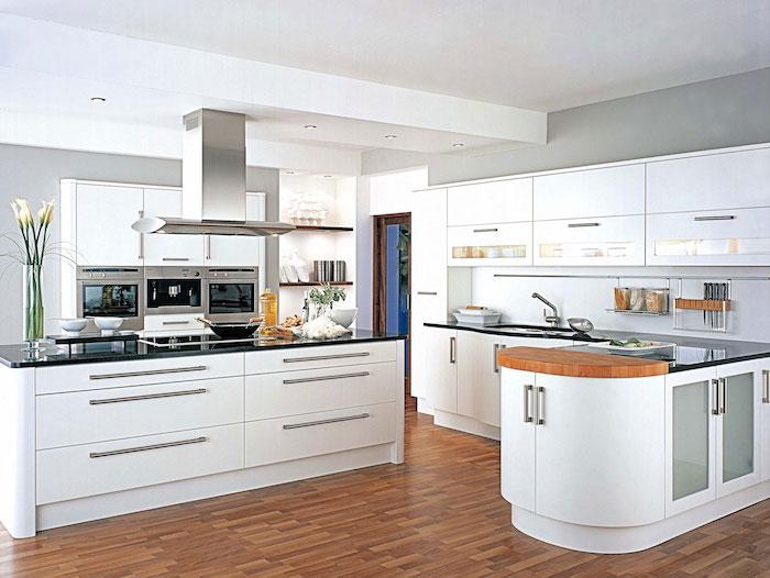 eine Wohnküche mit weißen Regalen eine Kochinsel und Laminat Boden, Blumen als Dekoration