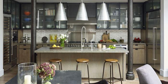 Wohnküche mit einer großen Kochinsel und drei Hocker und drei Lampen aus Aluminium