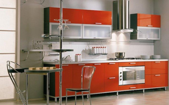 Wohnküche mit orangen Regalen, ein dreieckiger Tisch und moderne Stühlen