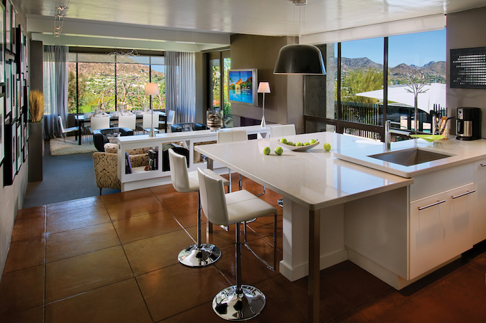 Offene Küche Mit Kochinsel Und Weiße Arbeitsplatte, Mit Treppen Von  Wohnzimmer Getrennt