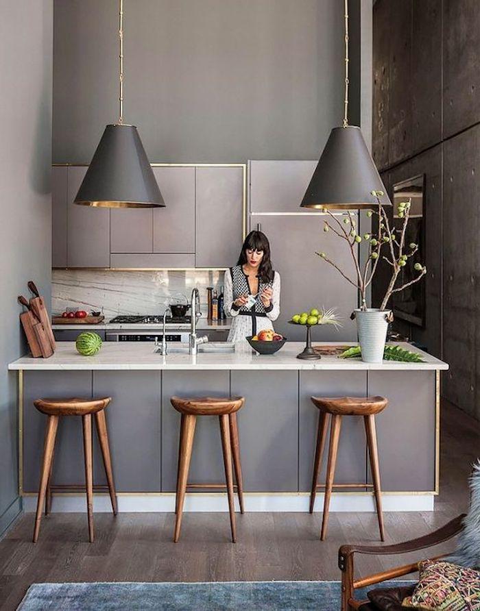 offene Küche in grauer Farbe mit zwei ausgefallenen Lampenschirmen, eine Frau bereitet den Nachtisch