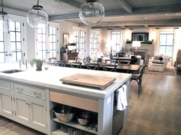 Offene Küche mit drei gerundeten Lampen und einen langen Esstisch, Wohnzimmer im Hintergrund