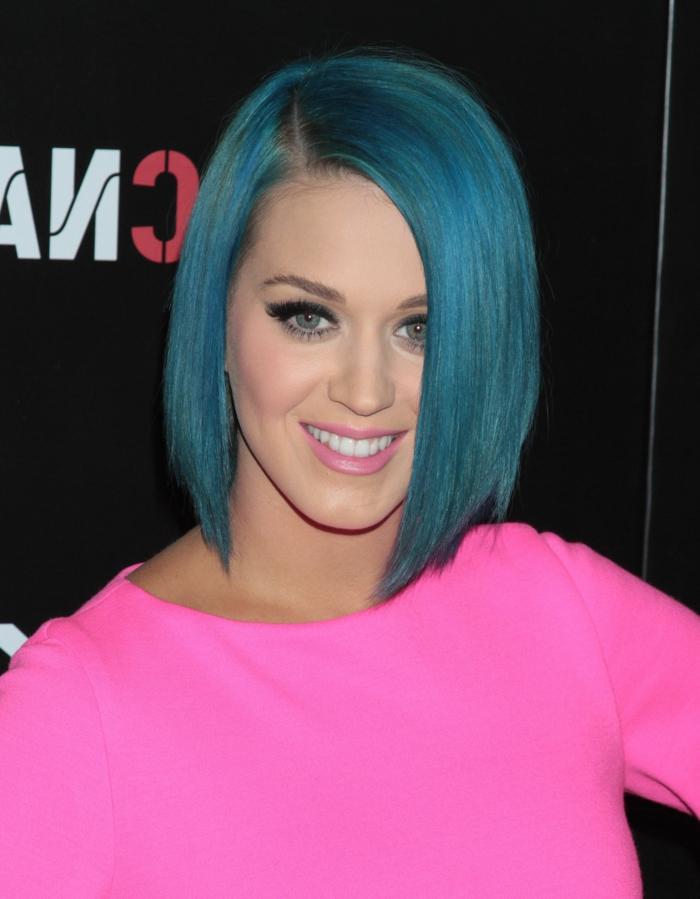 Katy Perry mit blauer Bob-Frisur, zartrosa Lippen, schwarze Mascara, Outfit in greller Farbe