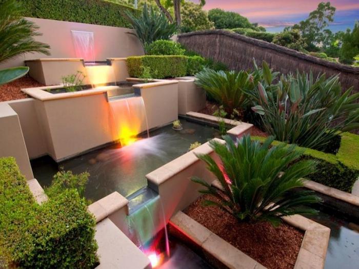 pflegeleichter garten, großer wasserfall mit beleuchtung, grüne pflanzen