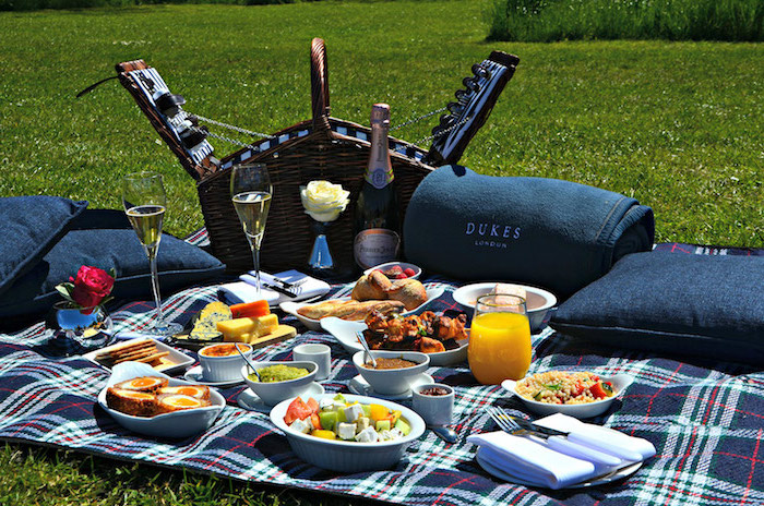 Picknick-Decke, Champagnenflasche, Salat, Dip, weiße Rose
