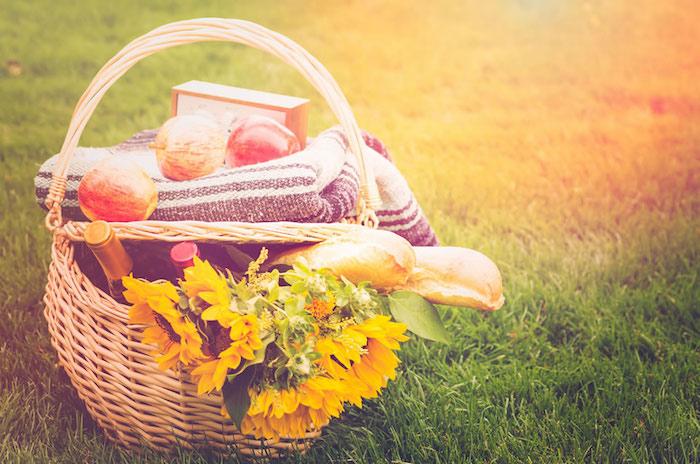 Weidenkorb mit zwei Stangenweißbroten, drei Äpfel, Blumen