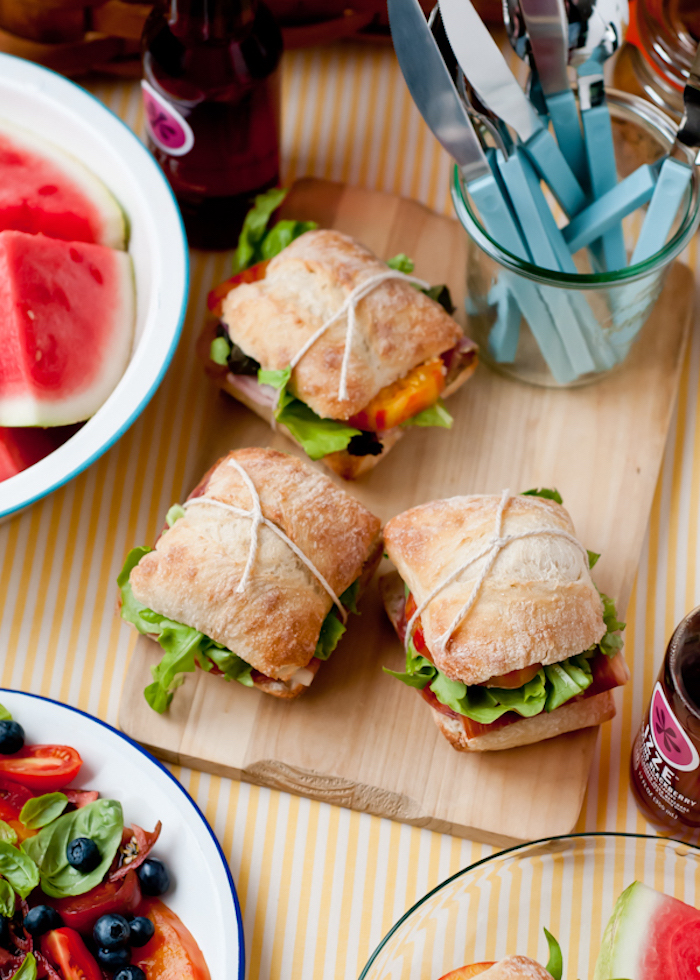 Sandwiches mit grünem Salat, blaues Plastikbestek, Wassermelone