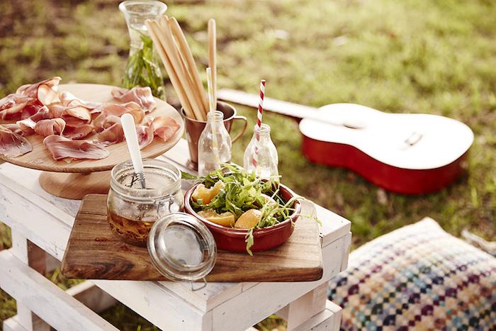 Kisse mit buntem Bezug, Salzstangen, Holzplatte, Limetten