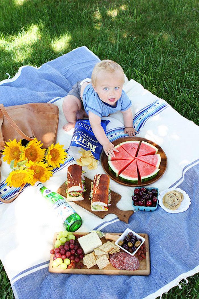 kleines Baby, eine Flasche Mineralwasser, Chips, blaue Verpackung