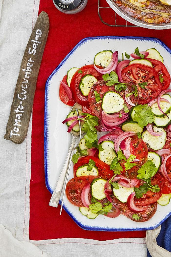 Salat mit roten Zwiebeln, Gurken, Tomaten, silbernes Besteck