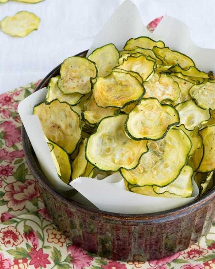 Gemüsechips aus Zucchini, braune Keramikschüssel, rote Decke
