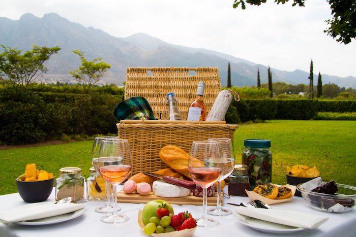 weiße Tischdecke, Weidenkorb, Brie-Käse, Rose-Wein, grüner Apfel, Bergaussicht