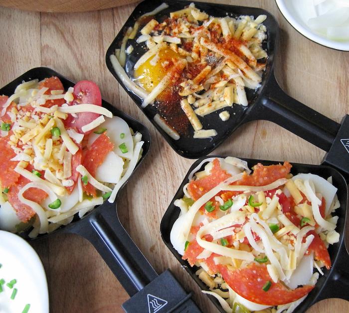 zutaten raclette pfannen tomaten erbsen geriebene käse salami kräuter eier kochen