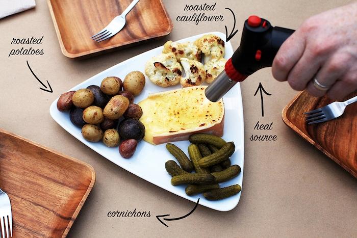 racletterezepte käse gurken kartoffel blumenkohl gabel teller aus holz raclette alternative