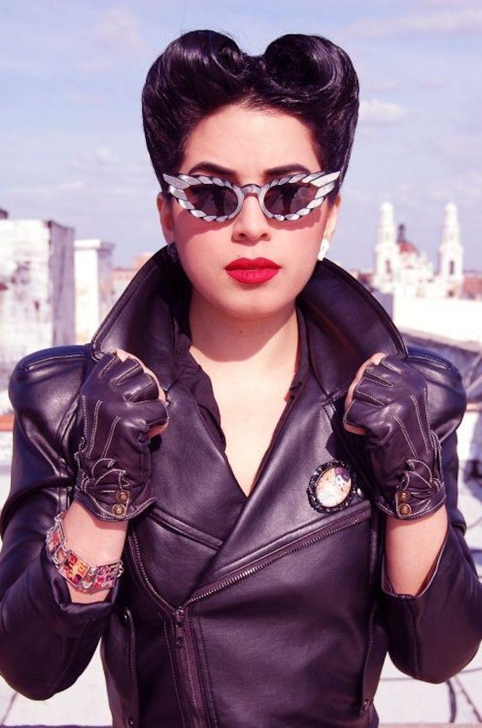 Rockabilly Frisur, schwarze Lederjacke mit einer Brosche, fingerlose Lederhandschuhe