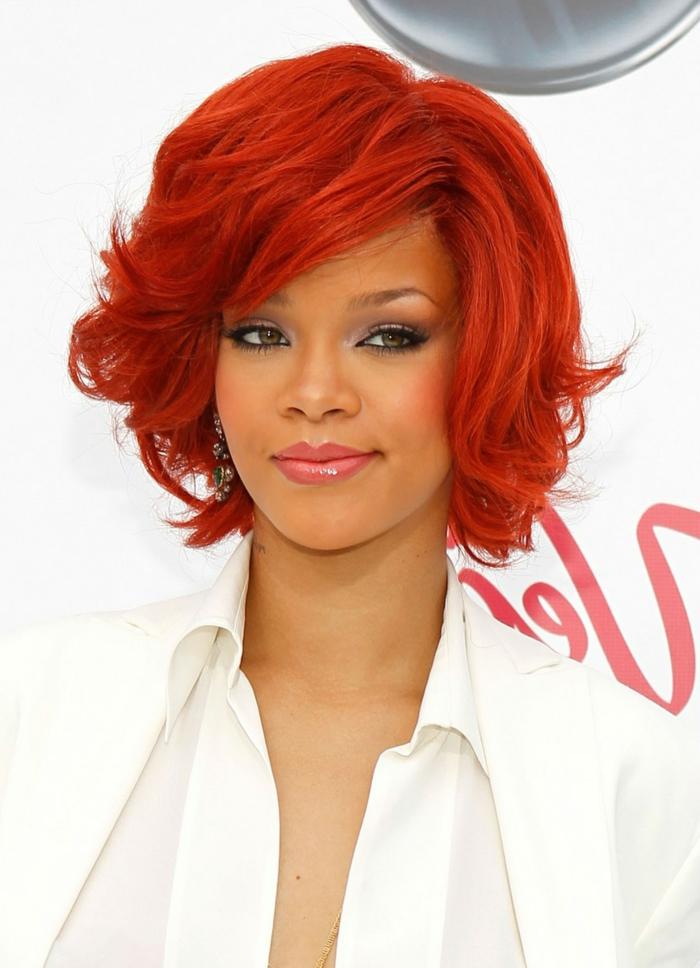 Rihanna mit roten Haaren, rote Haarfarbe und dunkler Teint, rosa Lippen, weißes Hemd