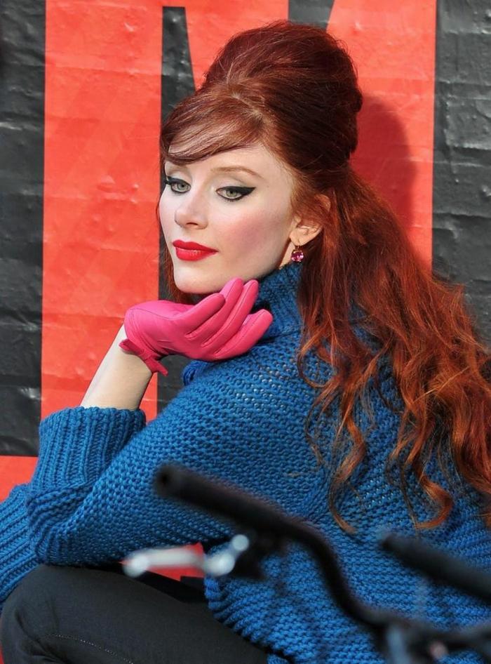 rote Haare, extravagante Haarfrisur, mit Pony, schöne Locken, blauer Pullover, rosa Armschuhe aus Leder