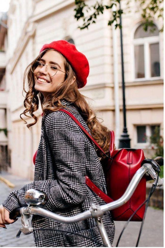 Gewellte hellbraune Haare, karierter Blazer, rote französische Mütze und Rucksack aus Leder