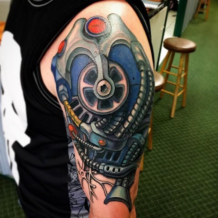 mann mit farbigem oberarm tattoo, tätowierung mit machinenteilen