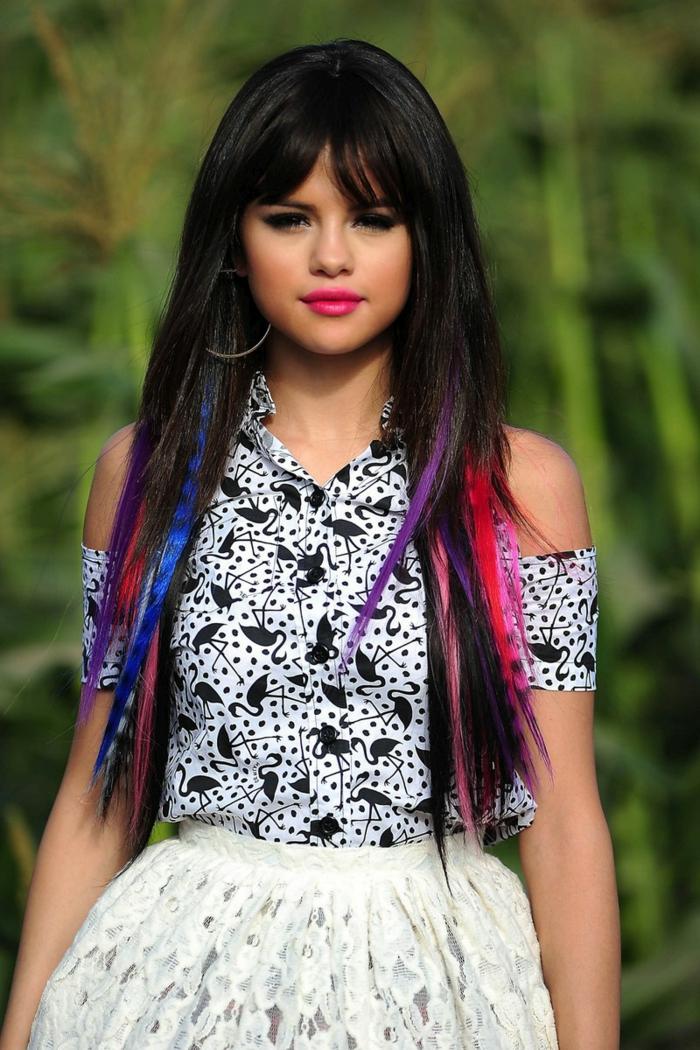Selena Gomez mit bunten Strähnen, langes Haar mit Pony, greller Lippenstift, schwarze Mascara
