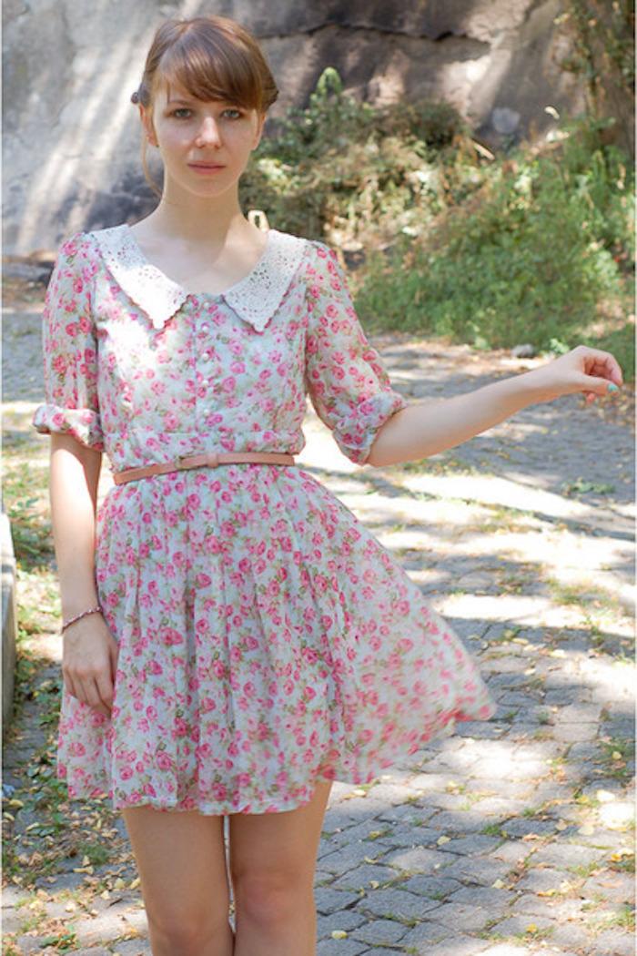 junges Mädchen mit kurzem rosa Kleid aus Tüll, braunem Ledergürtel, Spaziergang