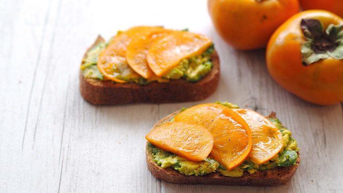 frphstück mit persimone, scheiben brot mit püree aus avocado und kaki früchten