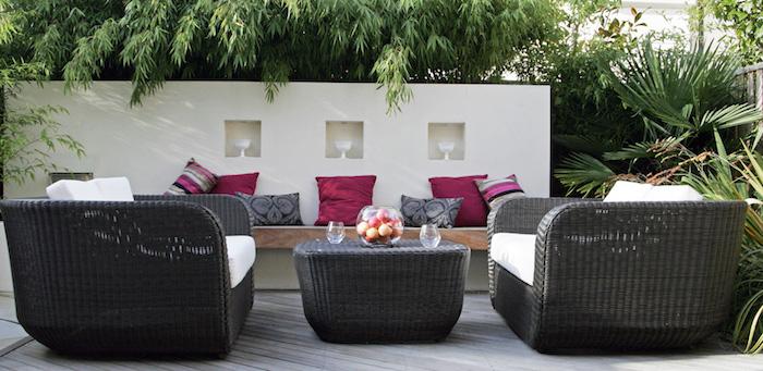 sitzplatz garten, große geflochtene sessel, dekokissen in rosa und grau