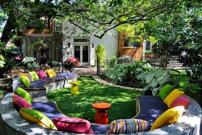 sitzplatz garten, runder sofa dekoriert mit vielen bunten dekokissen