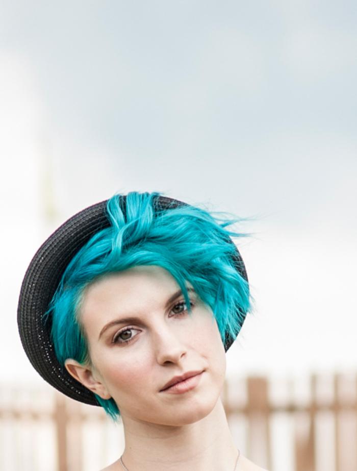 türkise Haare, Kurzhaarfrisur für Damen, schwarzer Hut, natürlicher Make-up, helle Haut