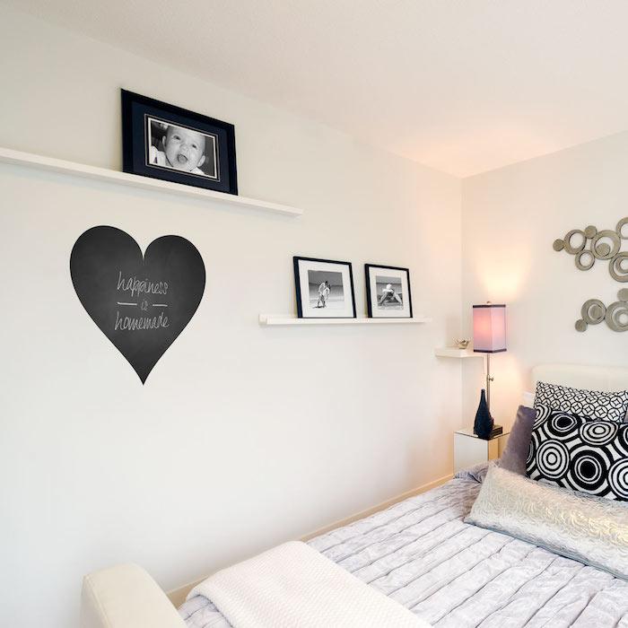 ein Herzchen aus Tafellack mit einer weißen Aufschrift in dem Schlafzimmer an der Wand voller Bilder
