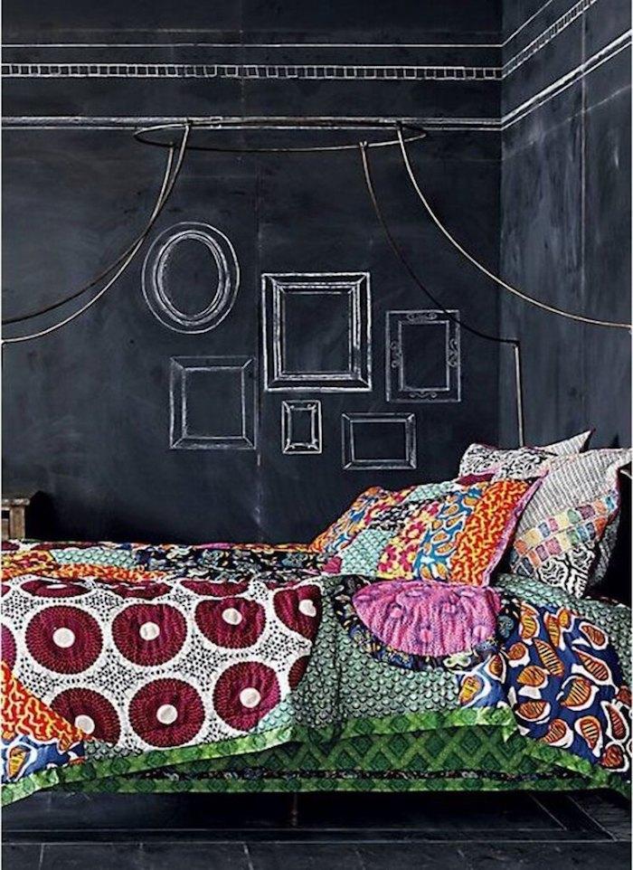 eine Wand mit Tafellack, darüber Bilderrahmen bemalt, ein Bett mit bunter Bettwäsche
