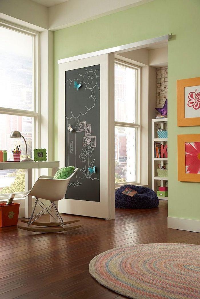 Tür in Tafelfarbe im Kinderzimmer mit einem lustigen Bild von einer Sonne und einem Baum
