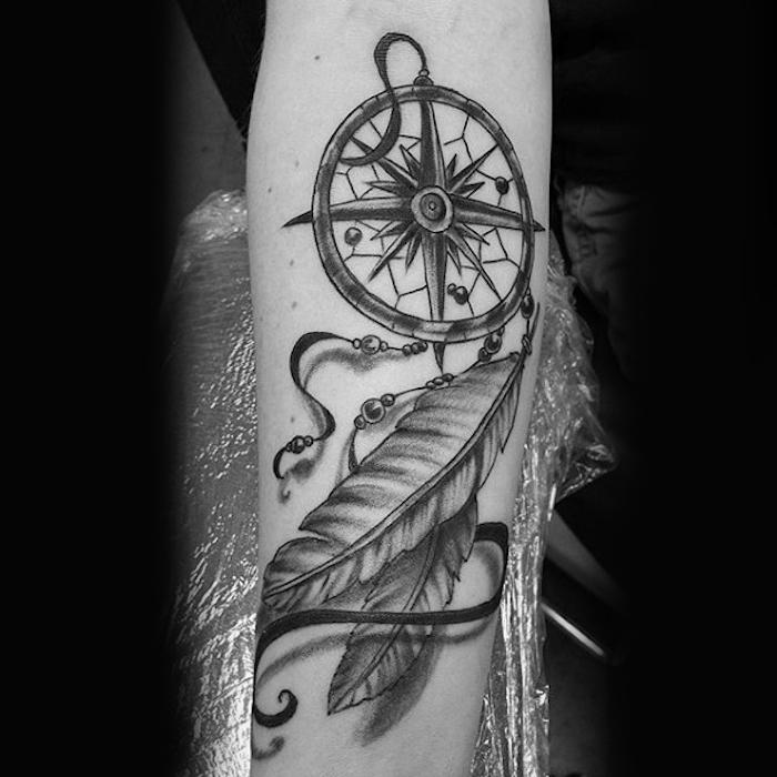 unterarm tattoo in schwarz und grau, traumfänger mit kompass und federn