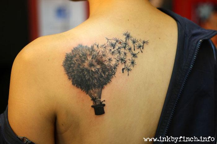tattoo symbole, frau mit tätowierung mit blumen-motiv am rücken