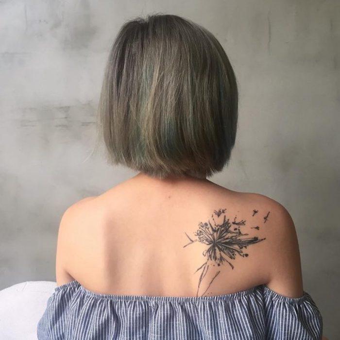 kleine tattoo motive, frau mit kurzen grauen haaren und tätowierung am rücken