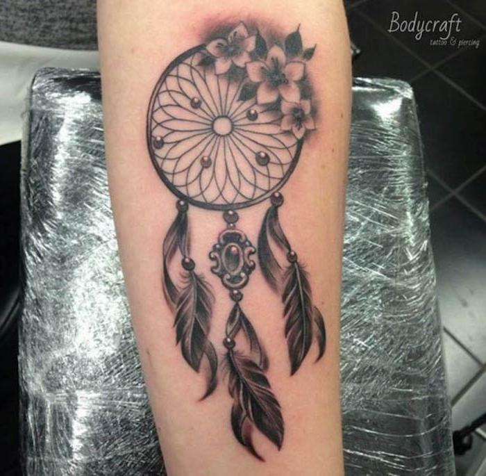 unterarm tattoo in schwarz und grau, traumfänger mit blumen und federn