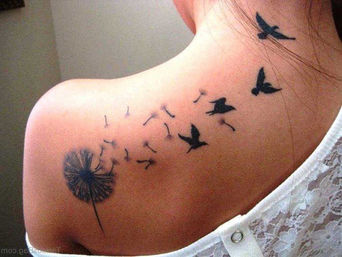frau mit vogel tattoo am rücken, pusteblume mit fliegenden samen und vögeln