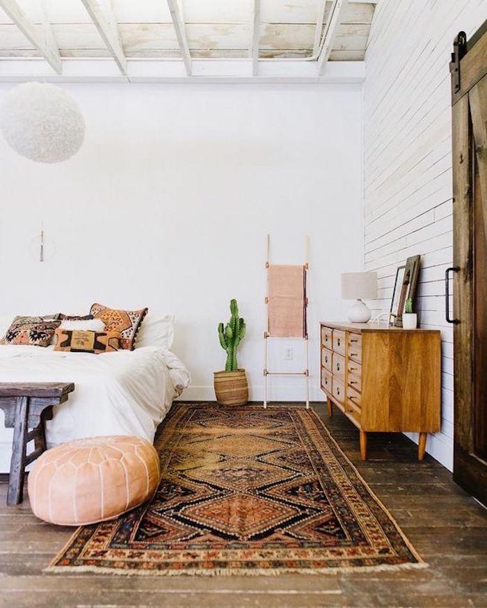 sitzkissen schlafzimer bett mit weißer bettwäsche bunte kissen und teppich schrank