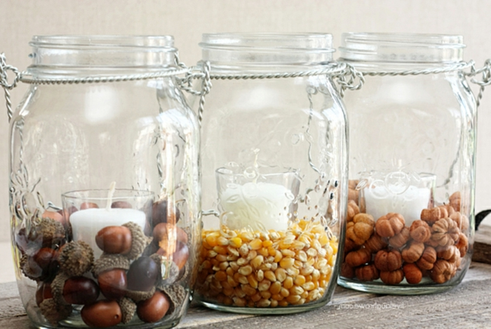 herbstliche Laternen selber machen, Einmachgläser mit Eicheln, Mais und Haselnüssen befüllen, weiße Duftkerzen